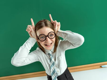 sassy: Naughty pupil making sassy funny expressions, showing horns her hands. Photo of teen school girl wearing glasses, creative concept with Back to school theme
