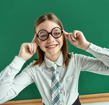disobedient: Smiling cheerful girl corrects his glasses. Photo of teen school girl wearing glasses, creative concept with Back to school theme Stock Photo