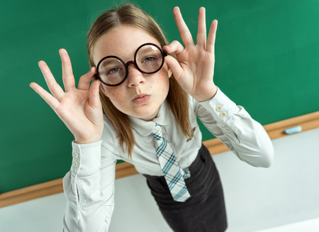women face stare: Student with an intelligent expression, correcting glasses. Photo of teen near blackboard, education concept