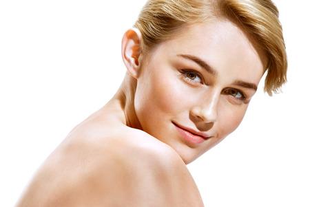 美しい少女の顔。完璧な肌。白い背景に魅力的なブロンドの女の子の写真。若さと肌ケアのコンセプト