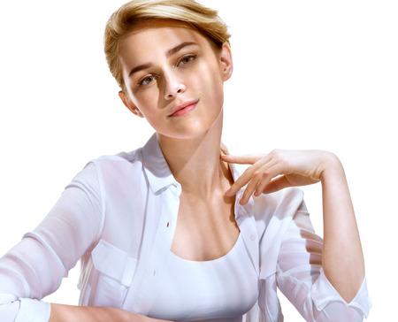 Mooi meisje met mooie make-up in wit overhemd, kijkt naar de camera. Foto van aantrekkelijke blonde meisje op een witte achtergrond. Jeugd en de huid zorgconcept
