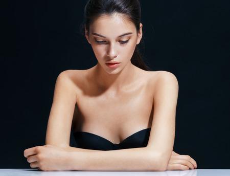 黒の背景に美しいブルネットの少女。欧州外観の魅力的な女性を閉じます。若さと肌ケアのコンセプト