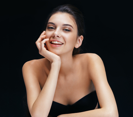Charming young girl on black background. Photo of smiling brunette with perfect make up. Archivio Fotografico