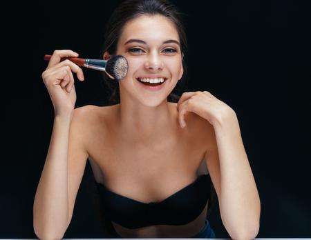 아름 다운 소녀와 그녀의 얼굴 근처 브러쉬를 확인 웃 고. 젊음과 피부 관리 개념