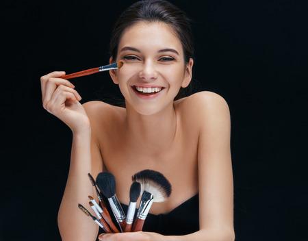 make up: Happy girl makes herself make up. Photo of brunette girl with brushes for make up on black background