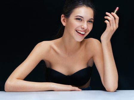 the well groomed: Happy brunette girl with lipstick on black background. Youth and skin care concept