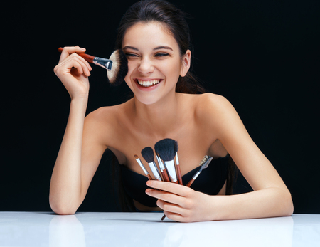 black makeup: Smiling brunette girl with make up brushes near her face. An attractive girl of European appearance on black background Stock Photo