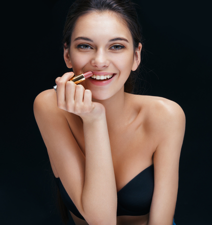 brunette girl: Beautiful brunette girl toothy smiling with lipstick. Close up of an attractive girl of European appearance on black background.