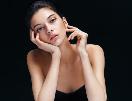 彼女の顔に触れるの完璧なメイクアップを持つ美しい少女。黒い背景にブルネットの女性のイメージ。若さと肌ケアのコンセプト