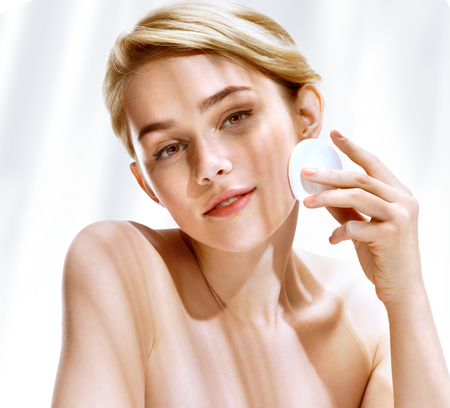 Young woman cleaning skin by cotton pad. Photo of attractive blonde girl in sunny summer day. Youth and skin care concept