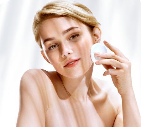 Jonge vrouw het reinigen van de huid door wattenschijfje. Foto van aantrekkelijke blonde meisje in het zonnige zomerdag. Jeugd en de huid zorgconcept Stockfoto