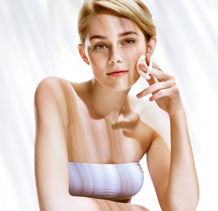 removing make up: Beautiful blonde girl removing make up from her face. Youth and skin care concept Stock Photo