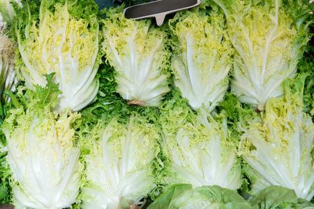 friso: manojos verdes de lechuga friso para la venta en un mercado