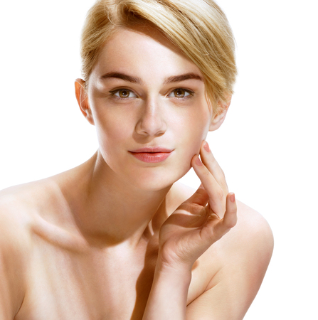 glowing skin: Beautiful spa woman touching her face. Close up of an attractive girl of European appearance on white background. Youth and Skin Care Concept.
