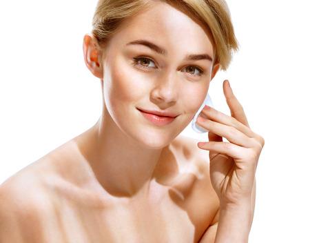 Mooie vrouw met een onberispelijke huid houdt wattenschijfjes in de buurt van gezicht. Jeugd en Skin Care Concept. Stockfoto