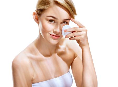 幸せな女は、白い背景の上のコットンで顔を洗浄します。若さと肌のケアの概念です。