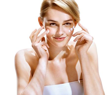 젊은 여자는 그녀의 예쁜 얼굴에 로션 크림을 적용의 초상화. 청소년 스킨 케어 개념입니다. 스톡 콘텐츠