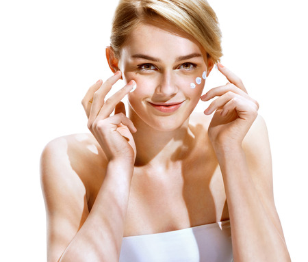 glowing skin: Portrait of young woman applying moisturizer cream on her pretty face. Youth and Skin Care Concept. Stock Photo