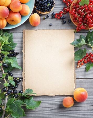 old paper background: Old paper with fresh fruits, berries and branches with currant  on wooden background. Close up, top view, high resolution product.