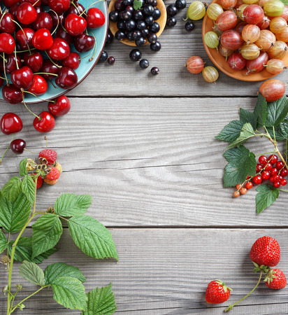 wooden table top view: Cherry, gooseberry, currant and green leaves on wooden table. Top view, high resolution product. Harvest concept.