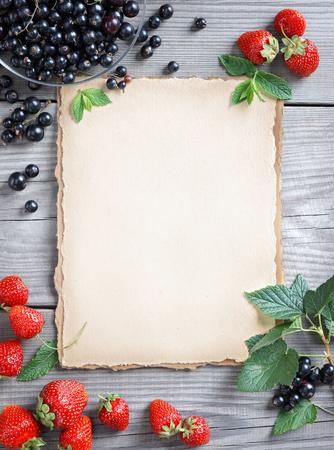 alimentos saludables: Fondo de la comida sana. papel viejo con la fresa y grosella en mesa de madera. espacio de la copia, vista desde arriba, un producto de alta resolución. concepto de la cosecha.