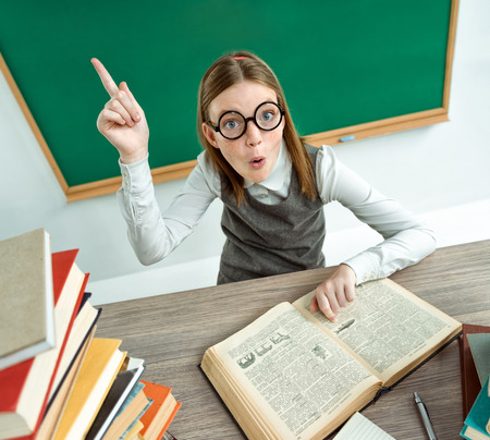 learner: Young learner having good idea, pointing finger up. Photo of teen school girl wearing glasses, creative concept with Back to school theme