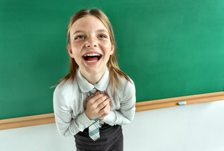 child laughing: Humorous high angle view of Happy joyful laughing beautiful girl with hands clasped together Stock Photo