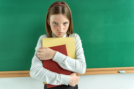 Upset little girl holding school books  photo of teen school girl, creative concept with Back to school theme Stock Photo