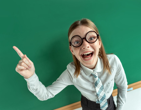 learner: Humorous high angle view of Young learner having good idea, pointing finger up. Photo of teen schoolgirl wearing glasses. Education concept