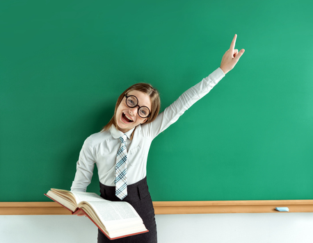 kids hand: Beautiful pupil girl with open book shows forefinger on the blackboard. Photo of student girl, creative concept with Back to school theme