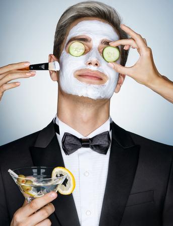 스파 얼굴 치료를받는 신사. 그의 얼굴에 그의 얼굴에 오이 페이셜 마스크와 잘 생긴 남자의 사진. 스스로 정리하기 스톡 콘텐츠