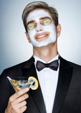 Dobre pielęgnacji skóry jest bardzo ważne. Szczęśliwy pan odbiera leczenie uzdrowiskowe twarzy. Zdjęcie z przystojny mężczyzna z twarzy maskę na twarzy i ogórka na oczy Zdjęcie Seryjne