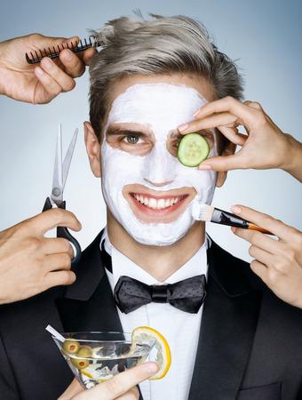 Gelukkig elegante man met een hydraterende gezichtsmasker omringd door de multifunctionele dienst (kapper, schoonheidsspecialiste, kapper). Foto van de gelukkige stijlvolle man krijgt de spa-behandelingen. Grooming zichzelf Stockfoto