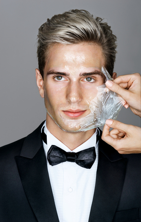hands off: Portrait of well dressed elegant man in facial mask on gray background. Womens hands beautician removes peeling off a facial mask from the mans face. Grooming himself