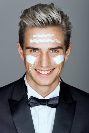 Belle homme avec des lignes de crème sur le visage, des soins spa. Close up de gentleman élégant sourire grassement. se toilettage.