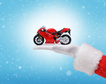 Hand in costume Santa Claus is holding red motorbike / studio shot of man's hand holding present / Merry Christmas & New Year's Eve concept / Closeup on blurred blue background. Archivio Fotografico