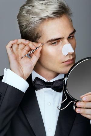 tweezing: Gentleman concentrating on tweezing his eyebrows. Photo of classy gentleman looking in the mirror, cares for his appearance. Grooming himself Stock Photo