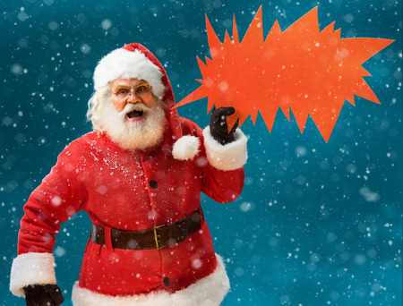 monstrous: Monstrous Santa Claus showing red sign speech bubble banner, looking unhappy and angry. Santa Claus on blue background. Merry Christmas & New Years Eve concept.