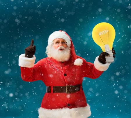 weihnachtsmann lustig: Vorübergehende Weihnachtsmann mit offenem Mund und Finger nach oben zeigt, Glühbirne Banner zeigt. Weihnachtsmann auf blauem Hintergrund eine gute Idee. Frohes neues Jahr! Lizenzfreie Bilder
