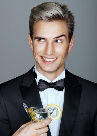 Es hora de ligar. apuesto hombre sonriente en traje negro con un vaso de martini. alta vida