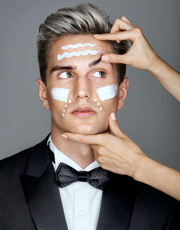 face lift: Face lift anti-aging treatment. Lifting effects of cream lotion or treatment on man. Photo of man in black suit on gray background. Skin care concept.