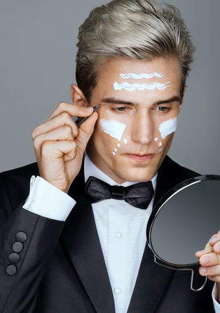 tweezing: Getting ready for the ball. Photo of handsome man tweezing the hair on his face. Wrinkle cream or anti-aging skin care cream. Grooming himself