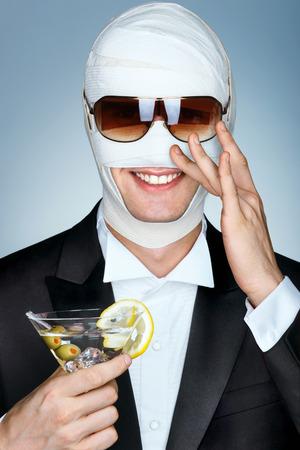 estrella de la vida: víctima de belleza con el vendaje en su cara después de cirugía estética. hombre de glamour en gafas de sol y con un vaso de cóctel de martini. concepto de cirugía plástica.