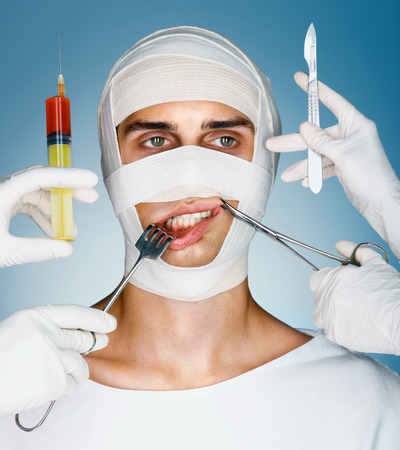 scalpels: Victim of plastic surgery. Man wrapped in medical bandages while doctors with syringes, surgical clamp, hook and scalpels near his face. Beauty concept