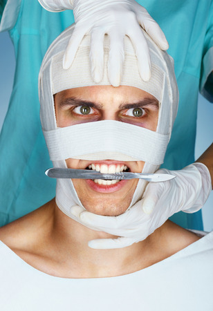 Furious beauty victim with scalpel in his mouth. Doctor of plastic surgery with the patient in medical bandage after operation. Plastic Surgery concept