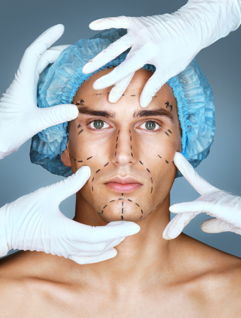 surgeons hat: Young man with many surgical hands. Patient with pencil marks on skin for cosmetic medical procedures. Surgical mark lines on eyes, nose, cheek, and jaw. Beauty face concept Stock Photo