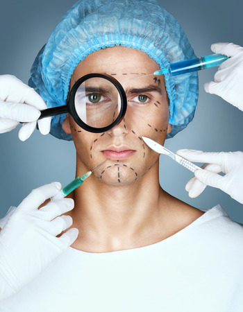 Handmade beauty. Portrait of male in medical headwear while four hands in medical gloves holding syringes and knifes close to his face Stock Photo