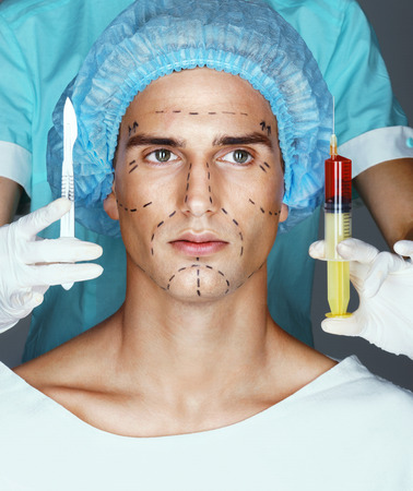 Nurse with syringe and scalpel near the face of the patient.  Attractive of male in medical headwear with pencil marks on skin for cosmetic medical procedures. Stock Photo