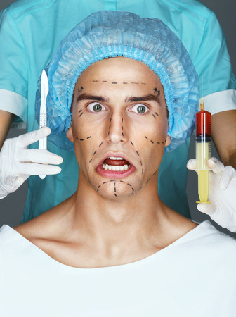 Nurse with syringe and scalpel near the face of the scared patient.  Mans face in medical headwear with pencil marks on skin for cosmetic medical procedures.