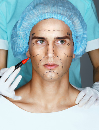 nurse hat: Doctor draws guideline marks on face of patient. Face of young man before plastic surgery. Beauty Face Stock Photo